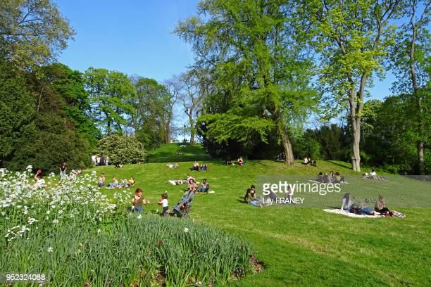 Gens sur la pelouse du parc des Buttes Chaumont au printemps 6 mai 2016 Paris France