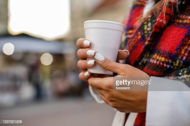 gentle female hands holding a plastic cup - white nail polish stock pictures, royalty-free photos & images
