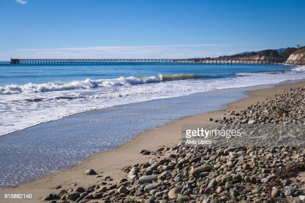 Gentle surf breaks on Haskell's Beach in Santa Barbara, California with industrial pier distant.