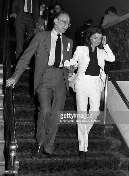 A gentleman carries the orange juice as he escorts Jacqueline Kennedy Onassis back to her seat during intermission at City Center