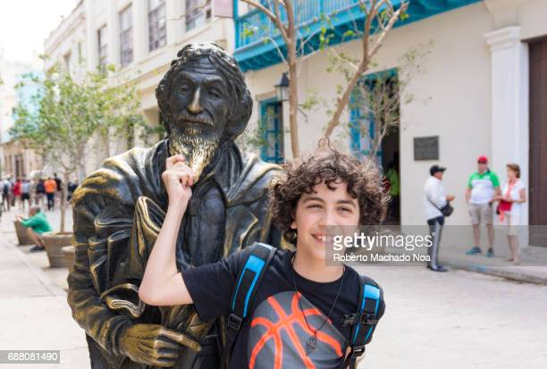 Gentleman from Paris bronze statue Young tourist boy with curly hair posing with a metal sculpture