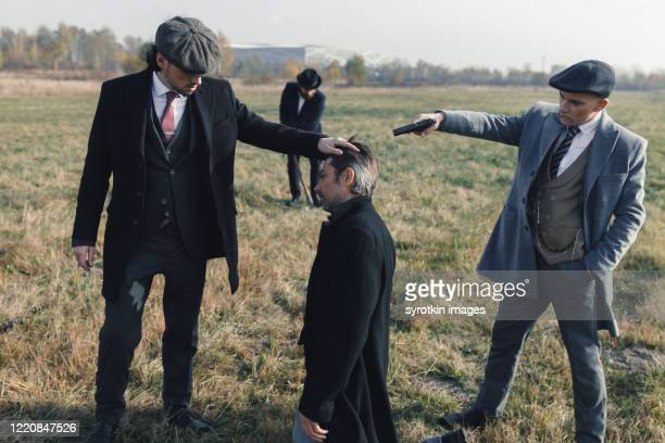 gentleman kneeling and preparing to own death. - dead gangster stock pictures, royalty-free photos & images