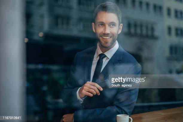 caballero en el descanso de café sosteniendo tarjeta de crédito - masculinidad moderna fotografías e imágenes de stock