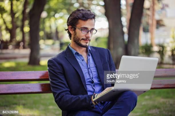 Gentleman sur ordinateur portable dans le parc