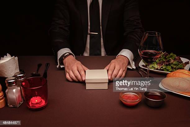 gentleman presenting a gift in restaurant - my lai sit fotografías e imágenes de stock