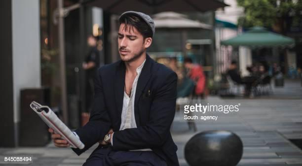 gentleman reading a magazine - coat foto e immagini stock