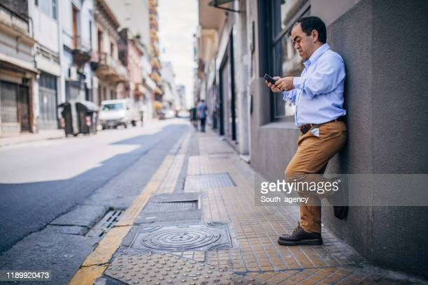 gentleman using mobile on the street - dwarf man stock pictures, royalty-free photos & images
