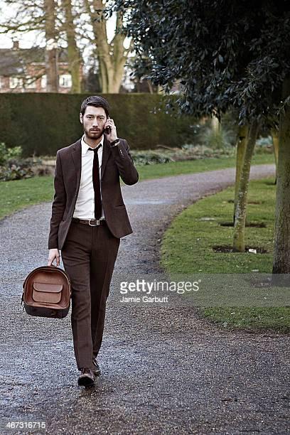 gentleman walking with a mobile phone - ツイード ストックフォトと画像