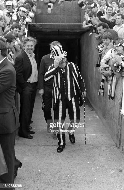Gentleman wearing a black three piece suit with white painted stripes and a black and white cane, tips his hat to supporters as he walks towards the...