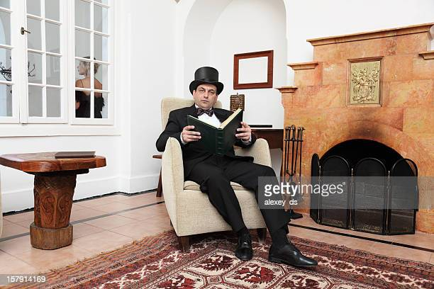 Gentleman with a book sits in armchair near fireplace