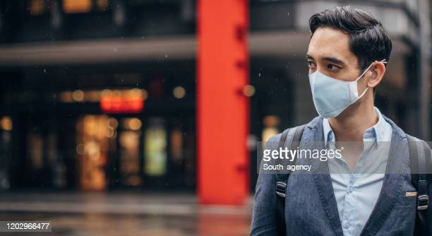 gentleman with in coronavirus infected city wearing a pollution mask - mascherina chirurgica foto e immagini stock