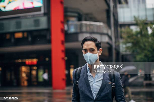 gentleman with in coronavirus infected city wearing a pollution mask - epidemic stock pictures, royalty-free photos & images