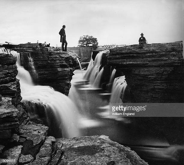 Gentlemen contemplate the beauty of the Chaudiere falls on the River Ottawa
