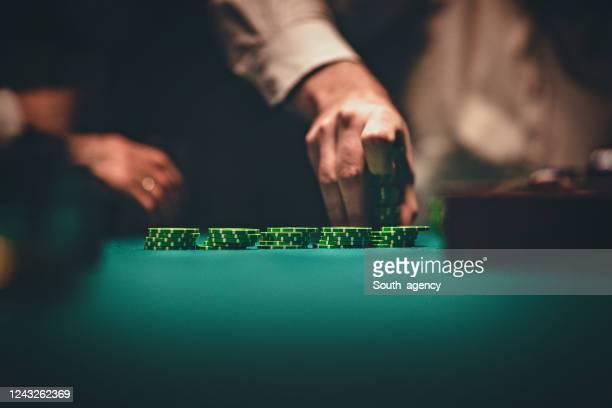 cavalheiros segurando fichas de jogo em cassino - poker - fotografias e filmes do acervo