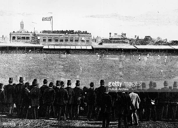 Gentlemen watching W G Grace bowling during a cricket match at the Oval, London.