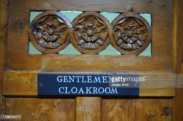 Gentlemens cloakroom sign on wooden door