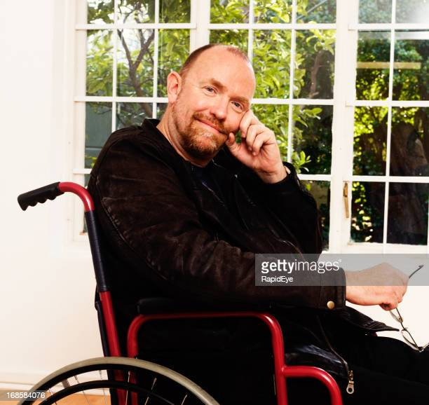 Gently smiling, serene man in wheelchair, apparently content with life