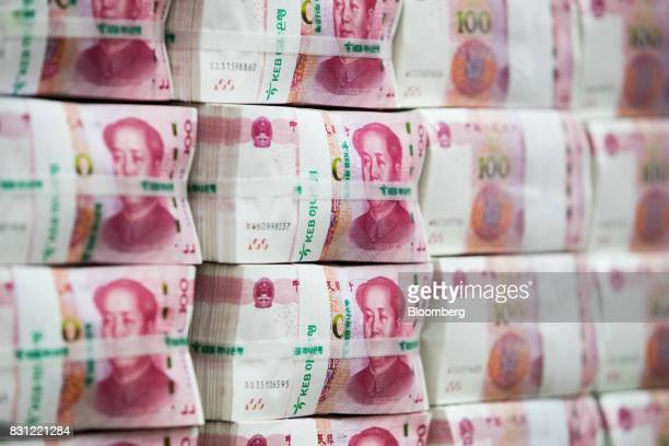 Genuine bundles of Chinese onehundred yuan banknotes are arranged for a photograph at the Counterfeit Notes Response Center of KEB Hana Bank in Seoul...