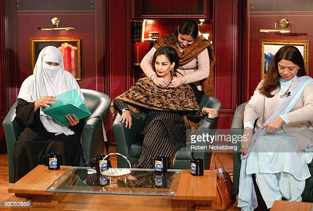 A Geo TV Islamabad Bureau producer attaches a remote microphone to opposition Parliament member Sherry Rehman as panelists representing the...
