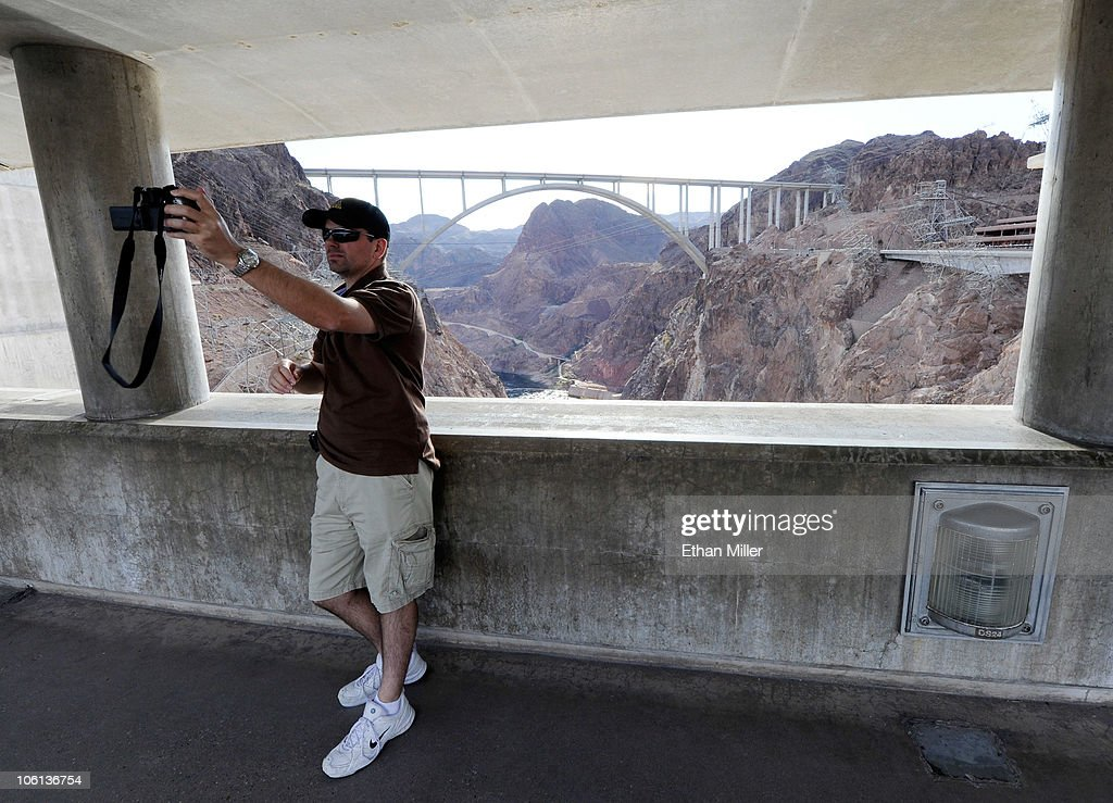 Geoff Anderson of Canada takes a photo of himself at the Hoover Dam with the Mike O'Callaghan-Pat Tillman Memorial Bridge part of the Hoover Dam Bypass Project visible in the background October 26, 2010 in the Lake Mead National Recreation Area, Nevada. The 1,900-foot-long structure sits 890 feet above the Colorado River, about a quarter of a mile downstream from the Hoover Dam. The USD 240 million four-lane bypass projects to relieve vehicle traffic on the Hoover Dam began in 2003, and opened to traffic on October 19.