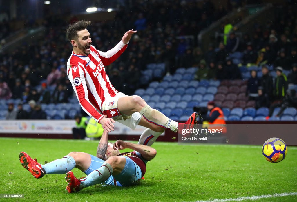 Geoff Cameron of Stoke City and Scott Arfield of Burnley clash in action during the Premier League match between Burnley and Stoke City at Turf Moor on December 12, 2017 in Burnley, England.