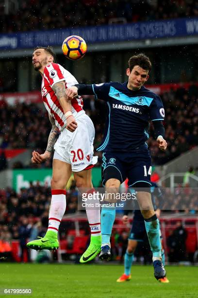 Geoff Cameron of Stoke City in action with Marten De Roon of Middlesbrough during the Premier League match between Stoke City and Middlesbrough at...