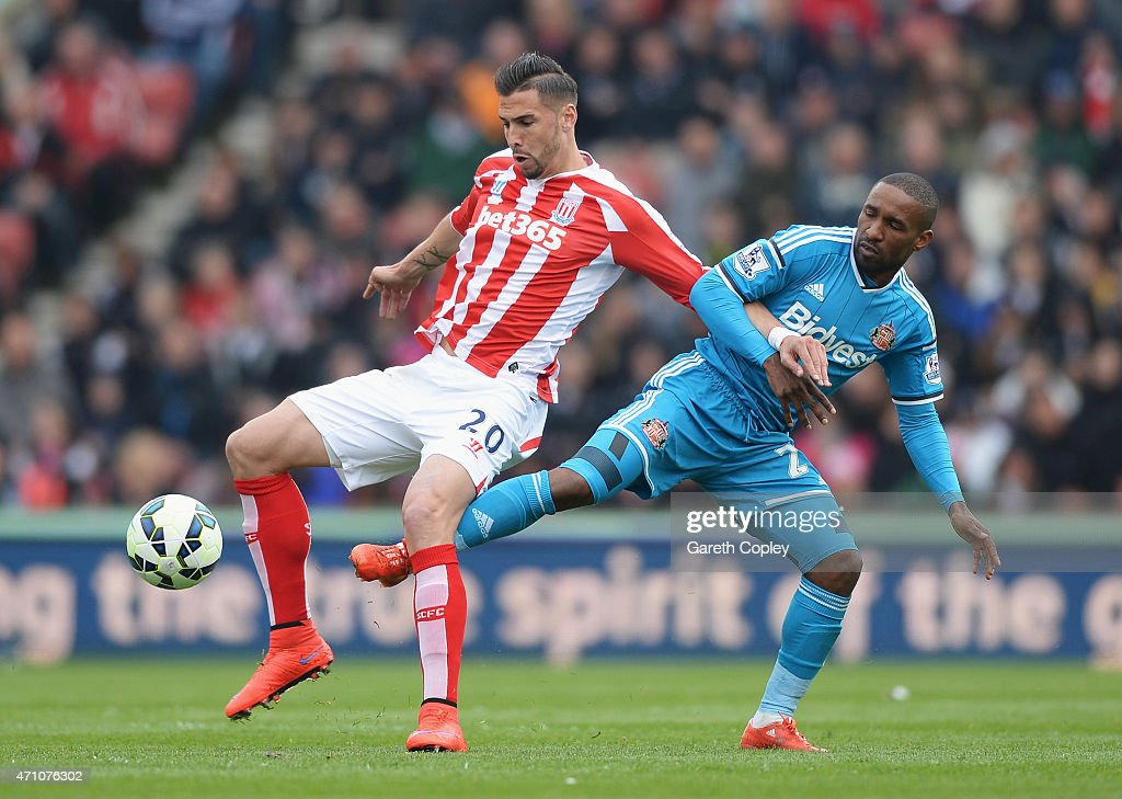 Geoff Cameron of Stoke City is challenged by Jermain Defoe of Sunderland during the Barclays Premier League match between Stoke City and Sunderland at Britannia Stadium on April 25, 2015 in Stoke on Trent, England.
