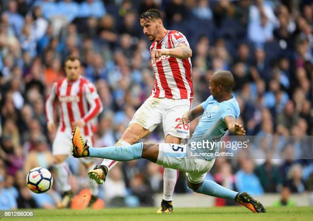 Geoff Cameron of Stoke City is tackled by Fernandinho of Manchester City during the Premier League match between Manchester City and Stoke City at...