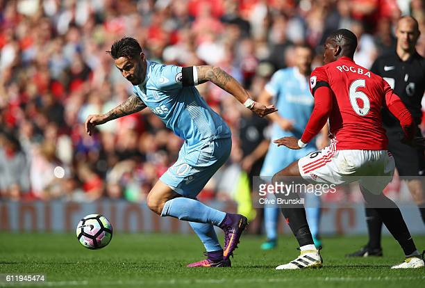 Geoff Cameron of Stoke City takes the ball past Paul Pogba of Manchester United during the Premier League match between Manchester United and Stoke...
