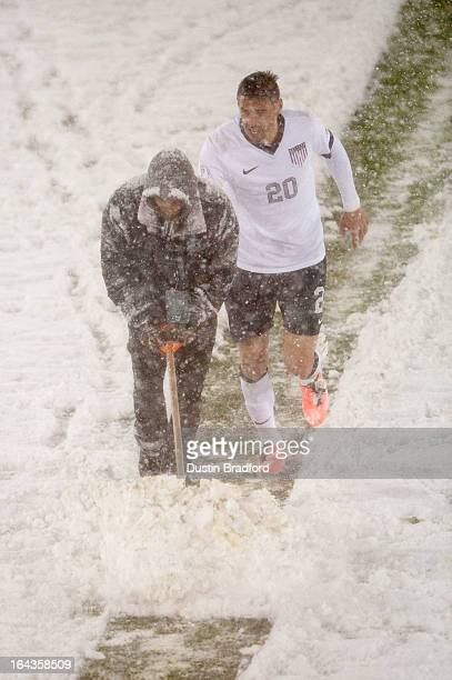 Geoff Cameron of the United States helps push snow by pushing on the back of an event staff person as he clears snow from midfield during a FIFA 2014...