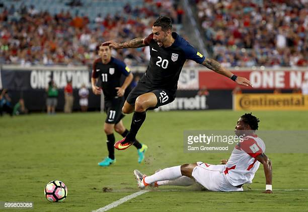 Geoff Cameron of the United States jumps over Mekeil Williams of Trinidad Tobago during the FIFA 2018 World Cup Qualifier against Trindad Tobago at...