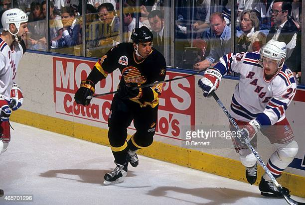 Geoff Courtnall of the Vancouver Canucks defends against Alex Kovalev and Sergei Zubov of the New York Rangers during Game 5 of the 1994 Stanley Cup...