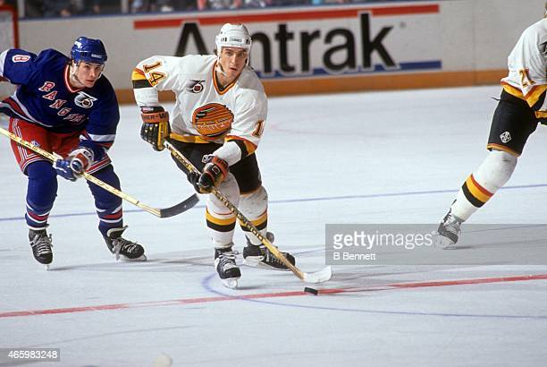 Geoff Courtnall of the Vancouver Canucks skates with the puck as Darren Turcotte of the New York Rangers follows behind during an NHL game on...