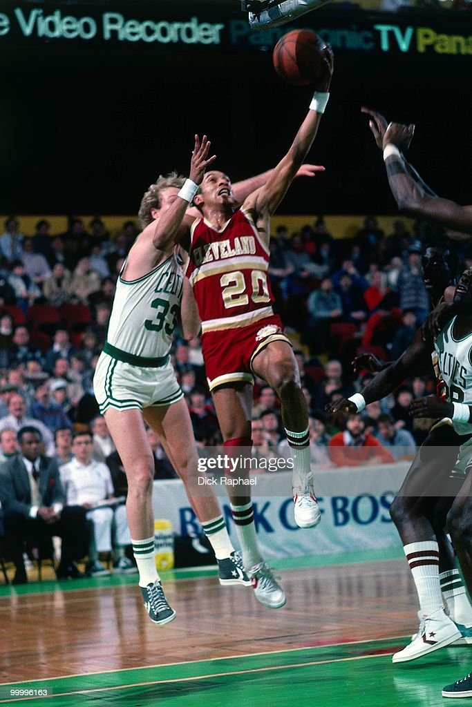 Geoff Huston #20 of the Cleveland Cavaliers shoots a layup against Larry Bird #33 of the Boston Celtics during a game played in 1983 at the Boston Garden in Boston, Massachusetts.