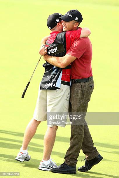 Geoff Ogilvy of Australia celebrates on the 18th hole with his caddie Cameron Ferguson after winning the Australian Open at The Lakes Golf Club on...