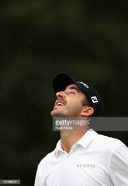 Geoff Ogilvy of Australia looks to the sky as rain falls during day one of the 2011 Emirates Australian Open at The Lakes Golf Club at The Lakes Golf...
