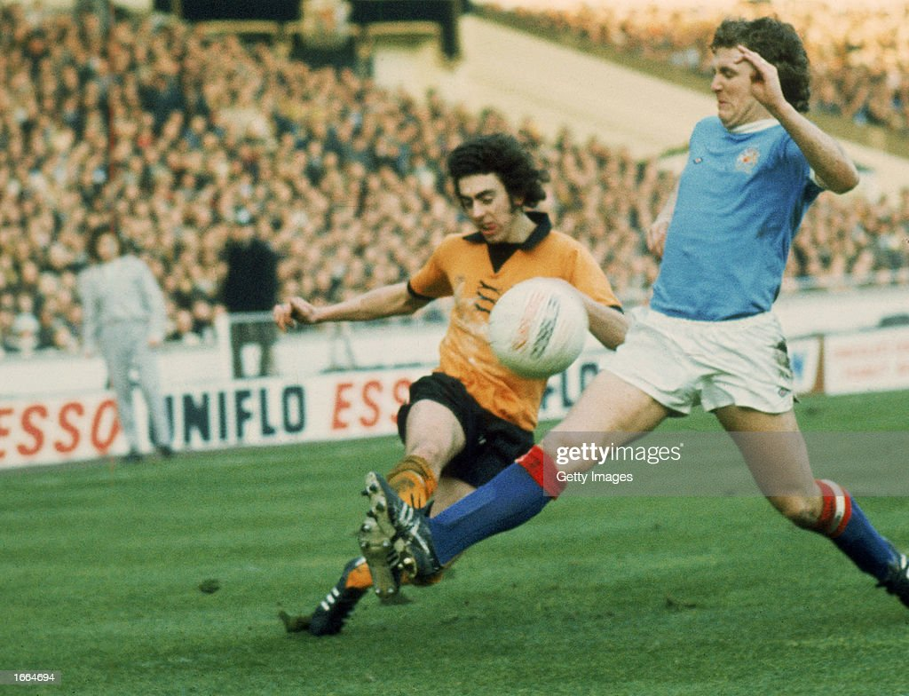 Geoff Palmer of Wolverhampton Wanderers crosses the ball as Tony Towers of Manchester City makes a challenge during the League Cup Final between Wolverhampton Wanderers and Manchester City held on March 2, 1974 at Wembley Stadium, in London. Wolverhampton Wanderers won the match and cup 2-1.