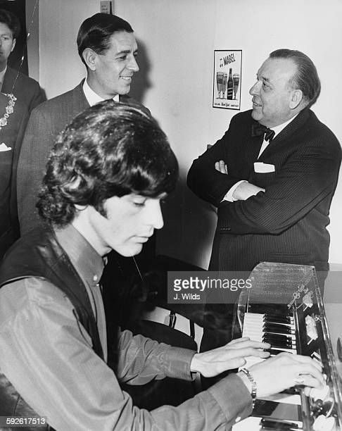 Geoff Unwin giving a demonstration of the Mellotron instrument as bandleader Geoff Unwin talks to Conservative politician Edward Du Cann in the...