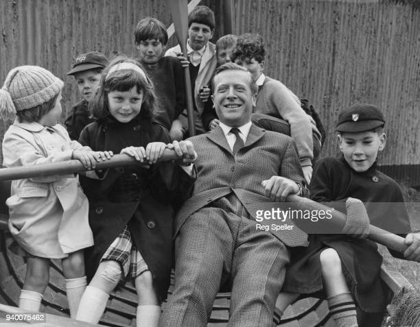Geoffrey JohnsonSmith the Conservative MP for East Grinstead rowing a group of children in a fishing boat in his constituency during Christian Aid...