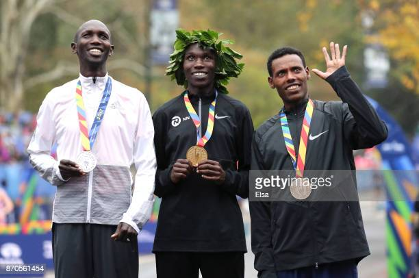 Geoffrey Kamworor of Kenya celebrates winning the Professional Men's Division with Wilson Kipsang of Kenya and Lelisa Desisa of Ethiopia during the...