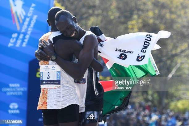 Geoffrey Kamworor of Kenya left embraces Albert Korir of Kenya after the two runners take first and second place respectively in the Men's Division...