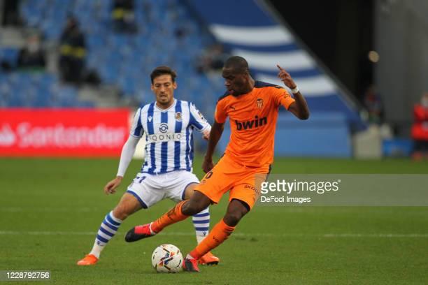 Geoffrey Kondogbia of FC Valencia and Adnan Januzaj of Real Sociedad battle for the ball during the La Liga Santander match between Real Sociedad and...