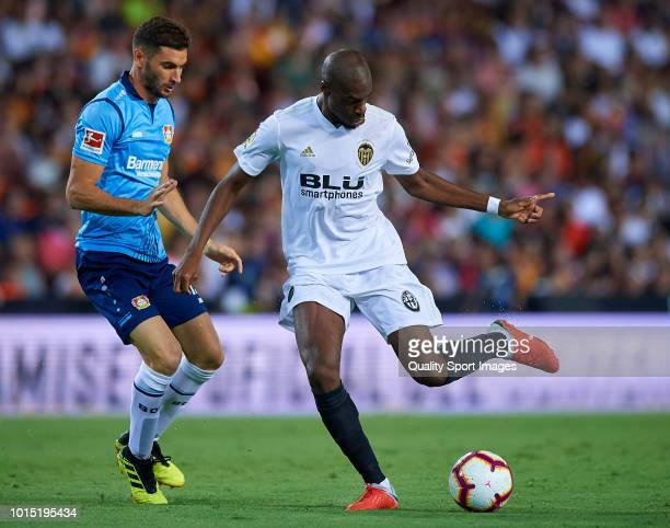 Geoffrey kondogbia of Valencia competes for the ball with Lucas Alario of Bayer Leverkusen during the preseason friendly match between Valencia CF...