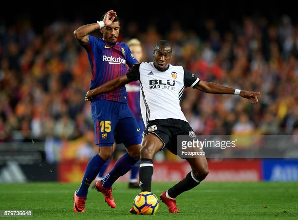 Geoffrey Kondogbia of Valencia competes for the ball with Paulinho of Barcelona during the La Liga match between Valencia and Barcelona at Estadio...