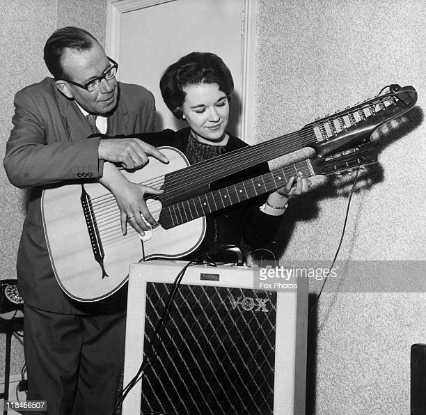 Geoffrey Sisley musician and teacher teaching one of his students Janet Ayres how to play a contraguitar a doublenecked guitar at Sisley's home in...