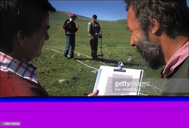 Geoffrey Summers and his wife Francoise study maps of the sub stratum made using a resistivity mofer operated by their two assistants The device...
