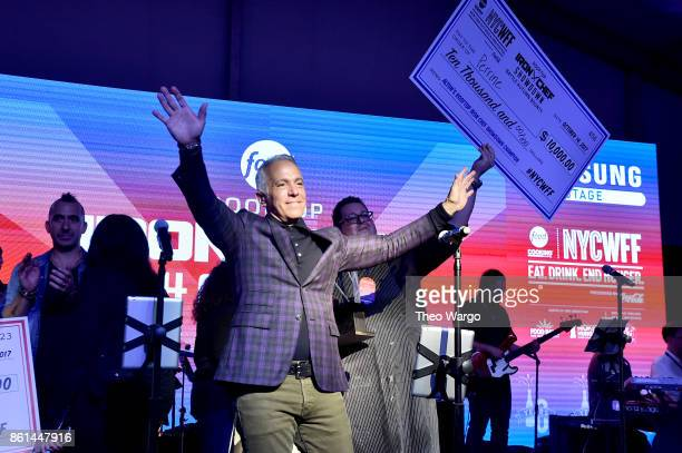 Geoffrey Zakarian waves onstage at the Food Network Cooking Channel New York City Wine Food Festival presented by CocaCola Rooftop Iron Chef Showdown...