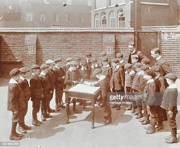 Geography lesson Hague Street School Bethnal Green London 1908 Two boys in the playground trying to find true north watched closely by their...