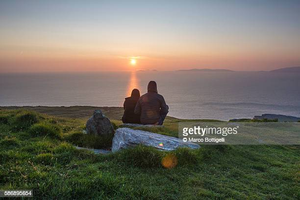 geokaun mountain, county kerry, munster province, ireland, europe. a couple watching the sun setting from the geokaun mountain and fogher cliffs. - coastline stock pictures, royalty-free photos & images