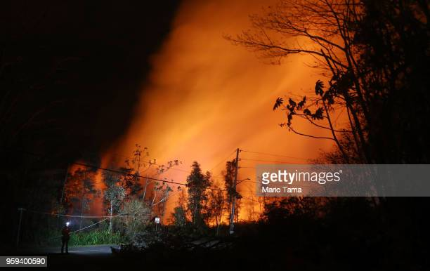geologist surveys lava illuminating volcanic gases from the Kilauea volcano at fissure 13 on Hawaii's Big Island on May 16 2018 in Pahoa Hawaii The...